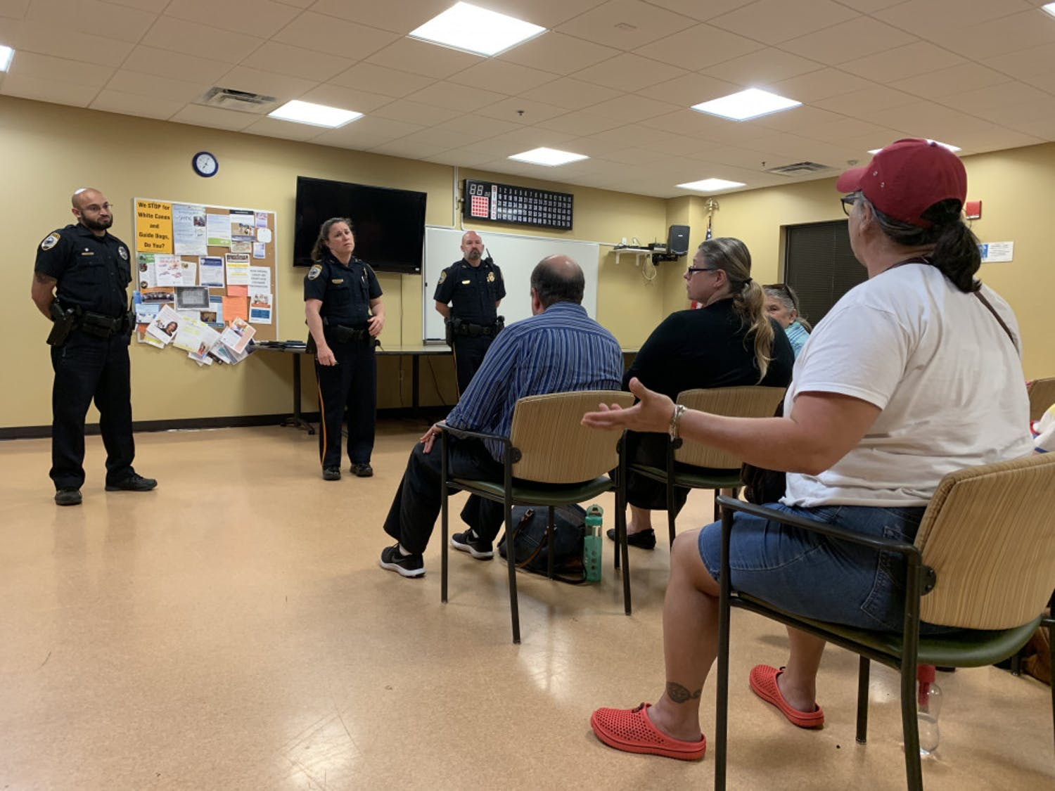 Gainesville resident Elizabeth Carrillo, 56, talks about recent dog attacks to three Gainesville Police officers at a neighborhood meeting Tuesday night.