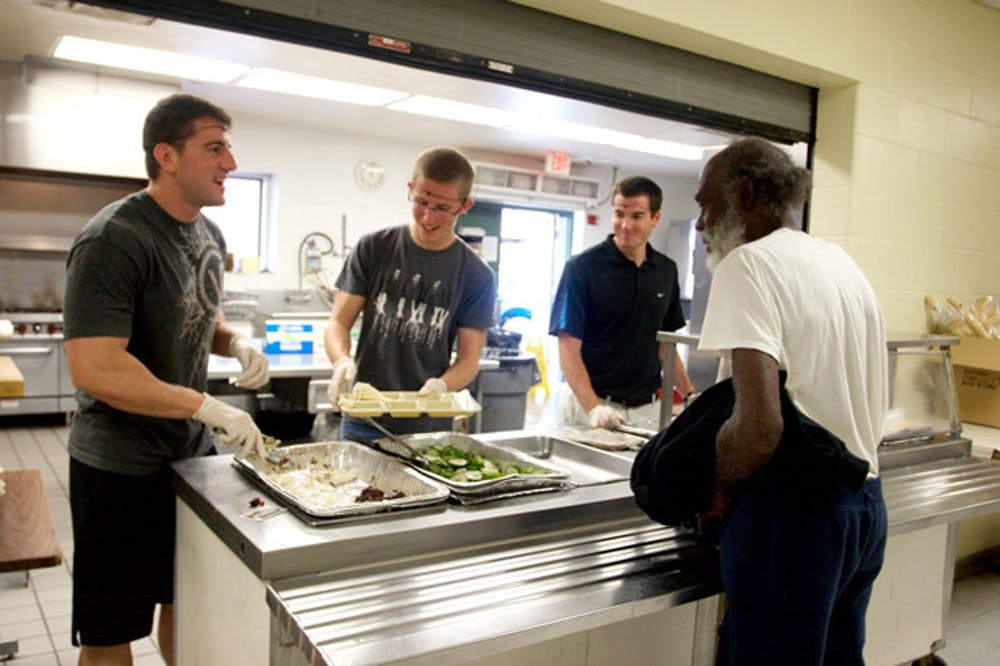 <p>Volunteering members of RecSports serve food to a man at St. Francis House on Thursday. Currently, St. Francis House is restricted to a 130-meal limit per day.</p>