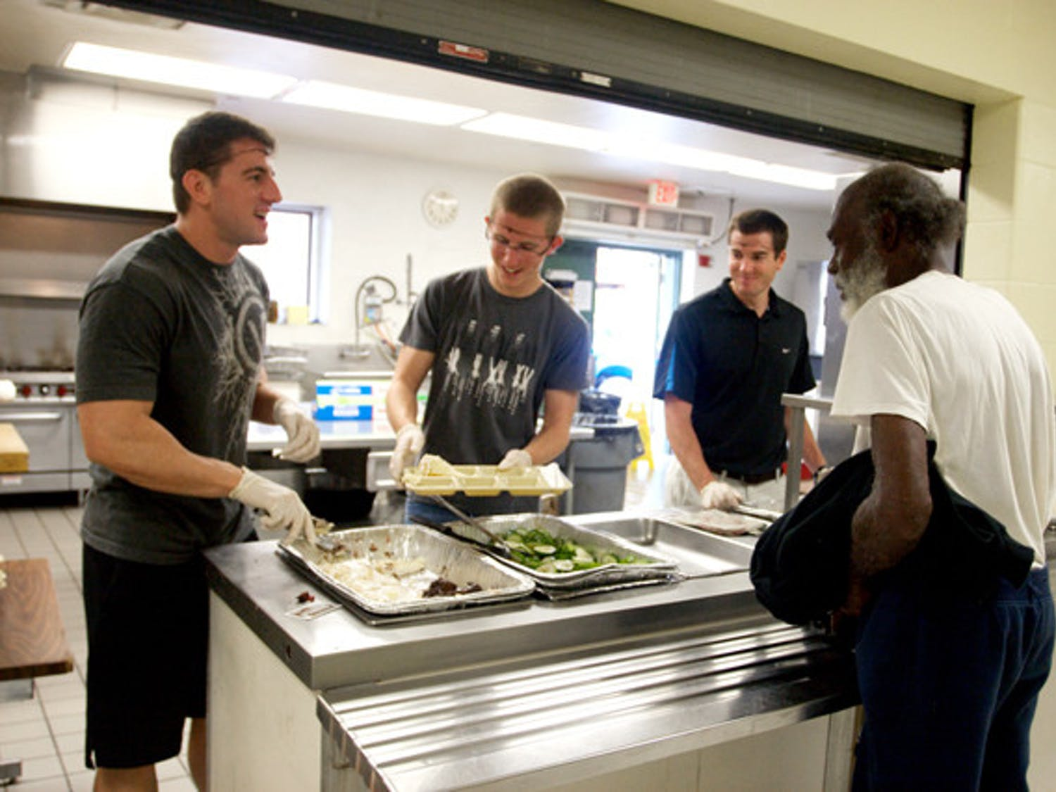 Volunteering members of RecSports serve food to a man at St. Francis House on Thursday. Currently, St. Francis House is restricted to a 130-meal limit per day.