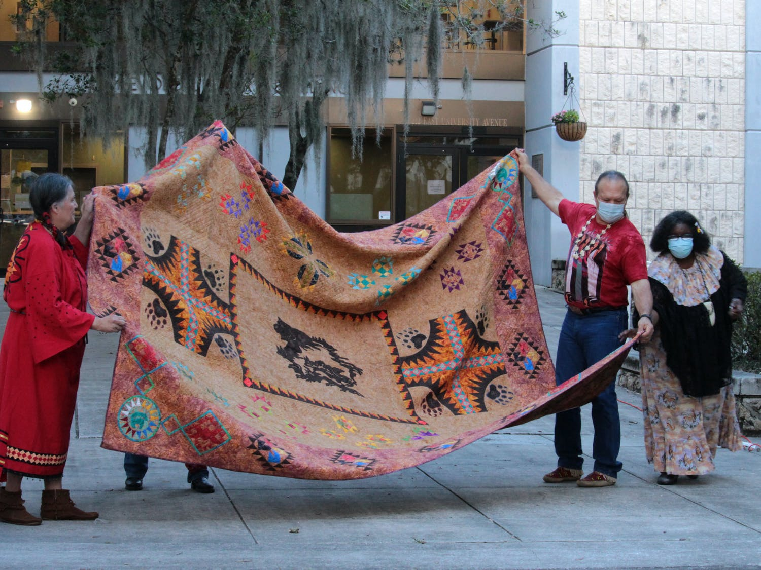 Dave Trezak (second from the right), Sioux tribe, helps to display a handmade, Native American quilt at Gainesville City Hall on Monday, Oct. 11, 2021.