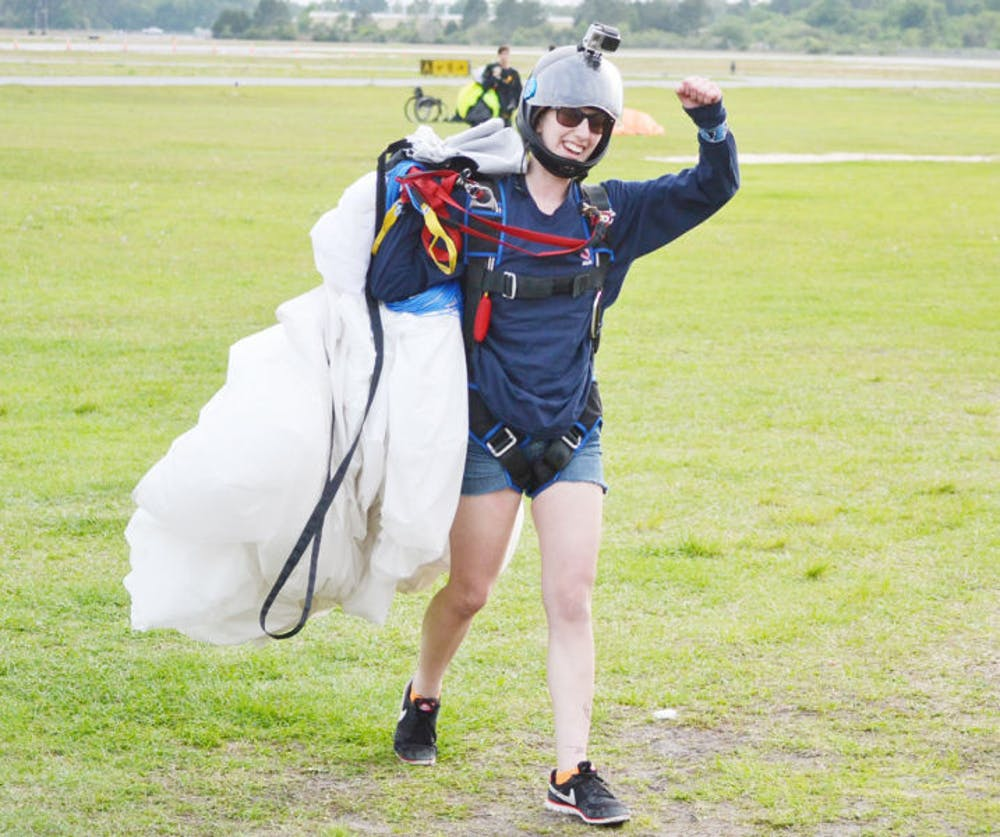 """<p dir=""""ltr"""">Maddie Sortino, a 21-year-old UF food science senior, celebrates after a jump during the UF Falling Gators' 16th Annual Skydiving Club Collegiate Boogie. The event took place Friday through Sunday at Kay Larkin Field at the Palatka Municipal Airport.</p>"""