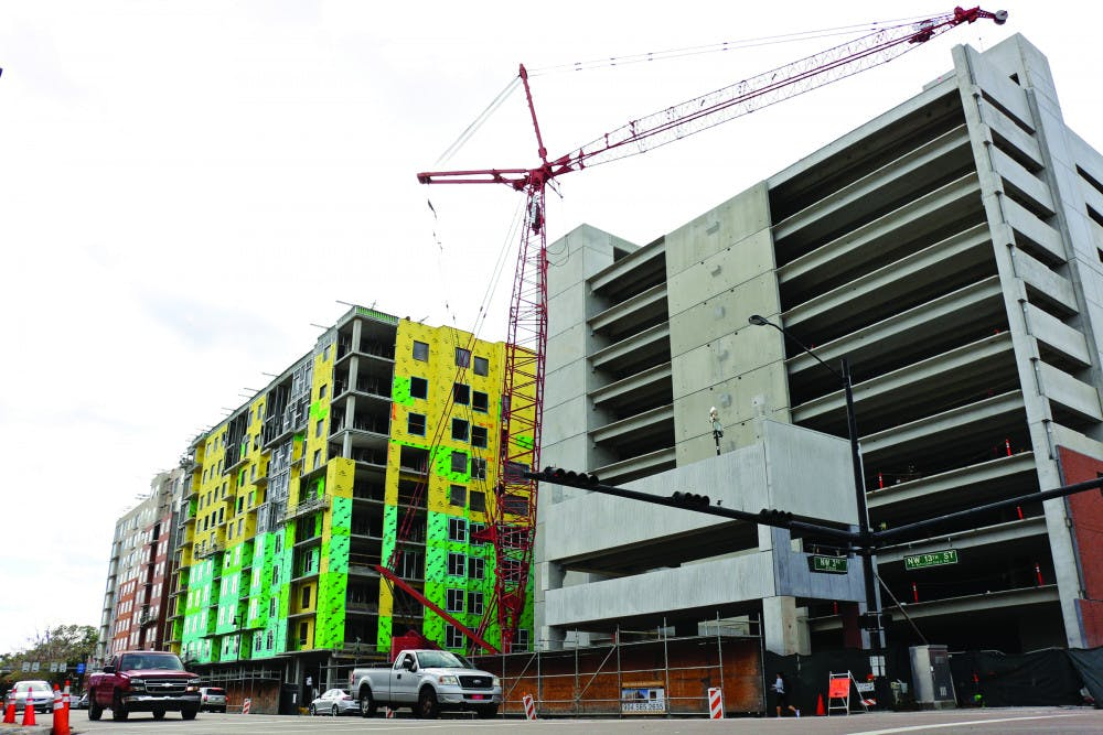 """<div class=""""page"""" title=""""Page 1""""><div class=""""layoutArea""""><div class=""""column""""><p><span>The three buildings of The Standard at Gainesville complex stand along 13th Street. From left: The fi</span><span>rst building will be for apartments, the second building will be an AC Hotels by Marriott, and the third building, which is near completion, will be a parking garage.</span></p></div></div></div>"""