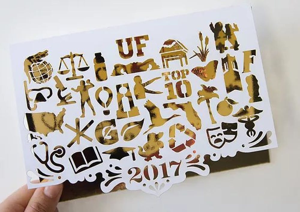 """<p><span id=""""docs-internal-guid-ef6b982c-2bc3-81ea-a532-b6149d99524b""""><span>The winning card features 32 icons, which represent categories that make UF unique, cut out on white paper over gold foil. The message inside the winning card reads """"Warmest Wishes,"""" which Jones described as a play on words about Florida's hot weather.</span></span></p>"""