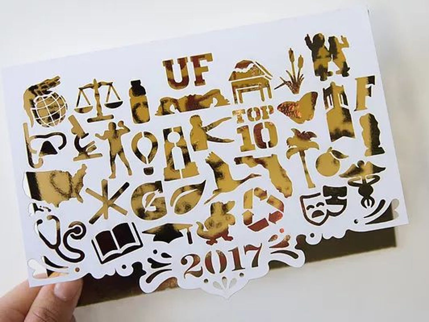 """The winning card features 32 icons, which represent categories that make UF unique, cut out on white paper over gold foil. The message inside the winning card reads """"Warmest Wishes,"""" which Jones described as a play on words about Florida's hot weather."""