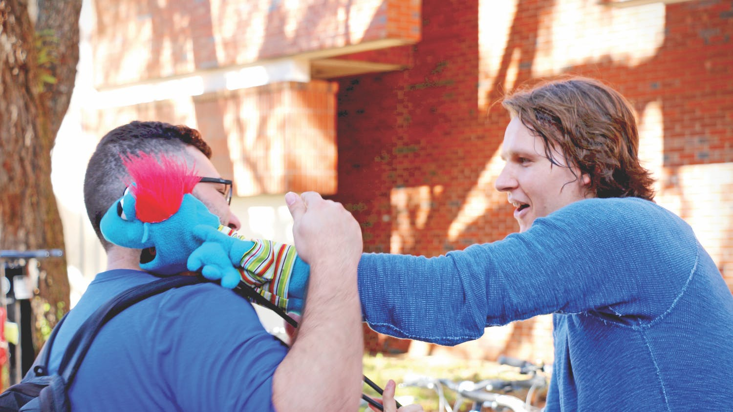 Tyrone, a foul-mouthed puppet controlled by Hippodrome State Theatre actor Jon Kovach, hugs Sammy Dahan, a 21-year-old UF biology senior, on Turlington Plaza on Wednesday.