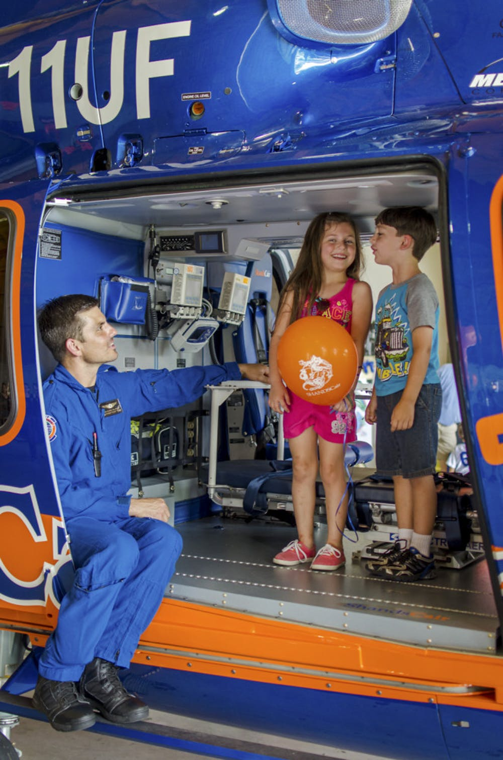 <p>Flight Paramedic Jesse Blaire, 37, shows Snow Whitman, 6, and her brother Blaze, 5, the interior of Shands Hostpial's new EC-155 helicopter. The new model can travel 45 mph faster and can accommodate an extra patient and crew member, improving their capability to transport patients. ShandsCair held an open house on Saturday to celebrate the new addition.</p>