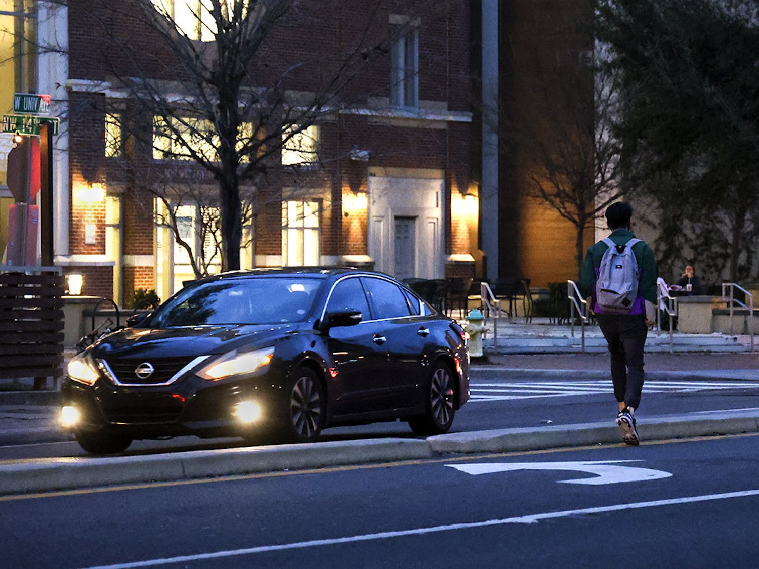 A pedestrian jaywalks across West University Avenue on Wednesday, Feb. 17, 2021.