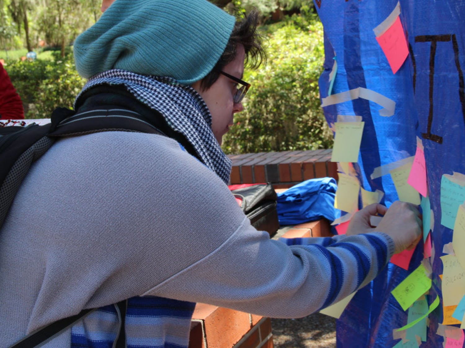 "Teresa Sellos, a UF computer science fifth-year, tapes a Post-It note to a Student Government's banner that reads ""What makes you diverse?"" on Monday on Turlington Plaza. The banner is part of a weeklong series of events hosted by Student Government called Diversity Week."