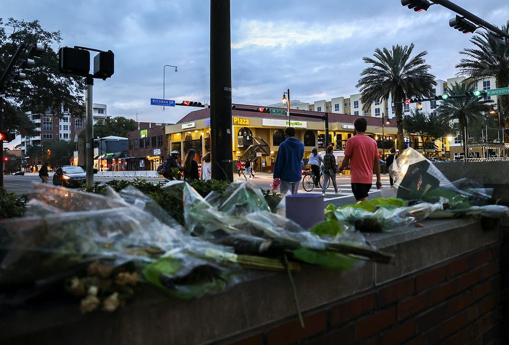 <p>Pedestrians cross West University Avenue on Wednesday, Feb. 17, 2021, near a memorial at the site of a car crash that killed Sophia Lambert, a UF student, in January.</p><p></p>