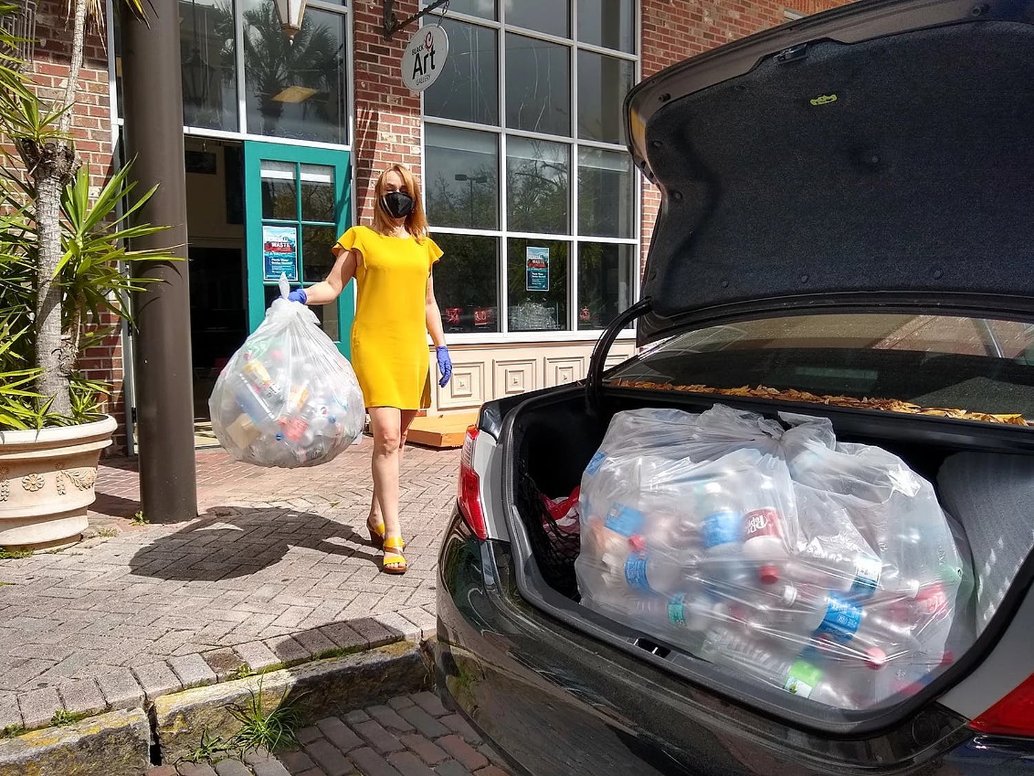 Iryna Kanishcheva holds recycled bottles in front of Black C Art Gallery. (Photo courtesy of Black C Art Gallery by Ani Collier)