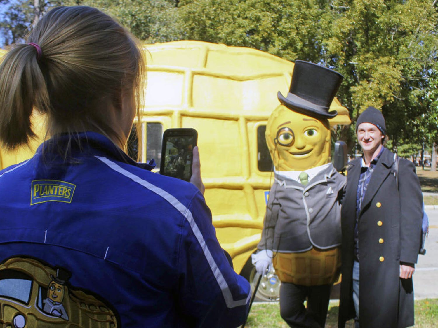 """Liz Johnson, a 23-year-old """"peanutter"""" who travels with the Planters NUTmobile, photographs Mr. Peanut and Billy Schap, a 22-year-old UF astronomy senior, near Plaza of the Americas on Thursday."""