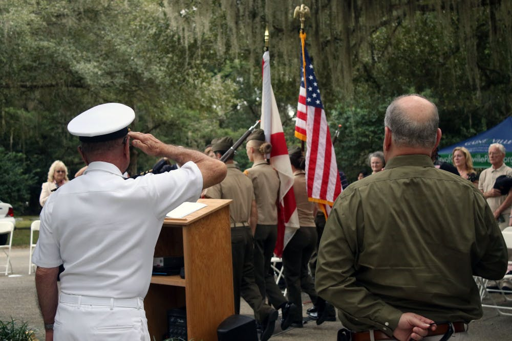 <p><span>Retired Lt. Commander Gary Cook (L) salutes the flag as the Milton Lewis Young Marines present the colors at a Veterans Day event at Evergreen Cemetery in Gainesville on Monday, Nov. 12, 2018. The event was held to honor the veterans buried in the cemetery and to commemorate the 100th anniversary of the end of World War One.</span></p>