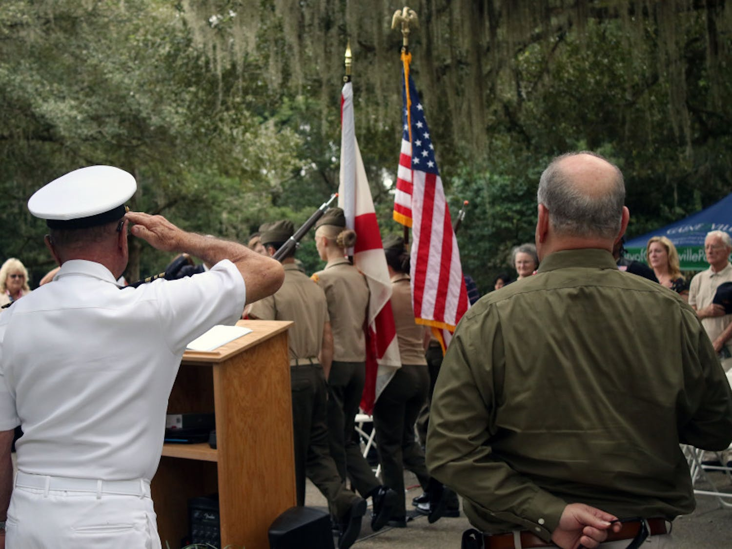 Retired Lt. Commander Gary Cook (L) salutes the flag as the Milton Lewis Young Marines present the colors at a Veterans Day event at Evergreen Cemetery in Gainesville on Monday, Nov. 12, 2018. The event was held to honor the veterans buried in the cemetery and to commemorate the 100th anniversary of the end of World War One.