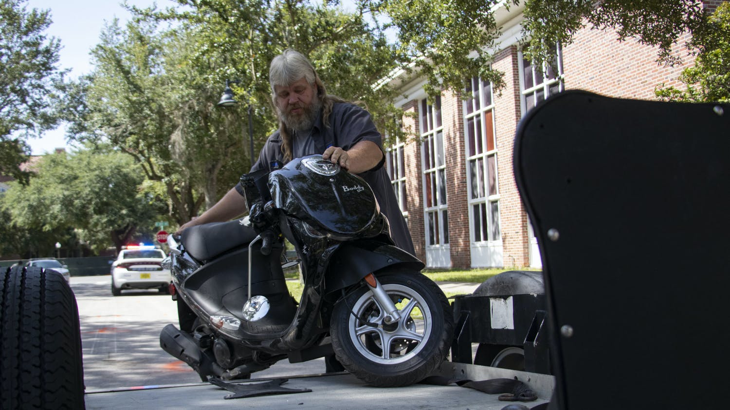 William Edwards, Elite Towing tow truck driver, puts the scooter involved in the crash on Northwest 16th Street on his trailer on Monday, Aug. 30, 2021.