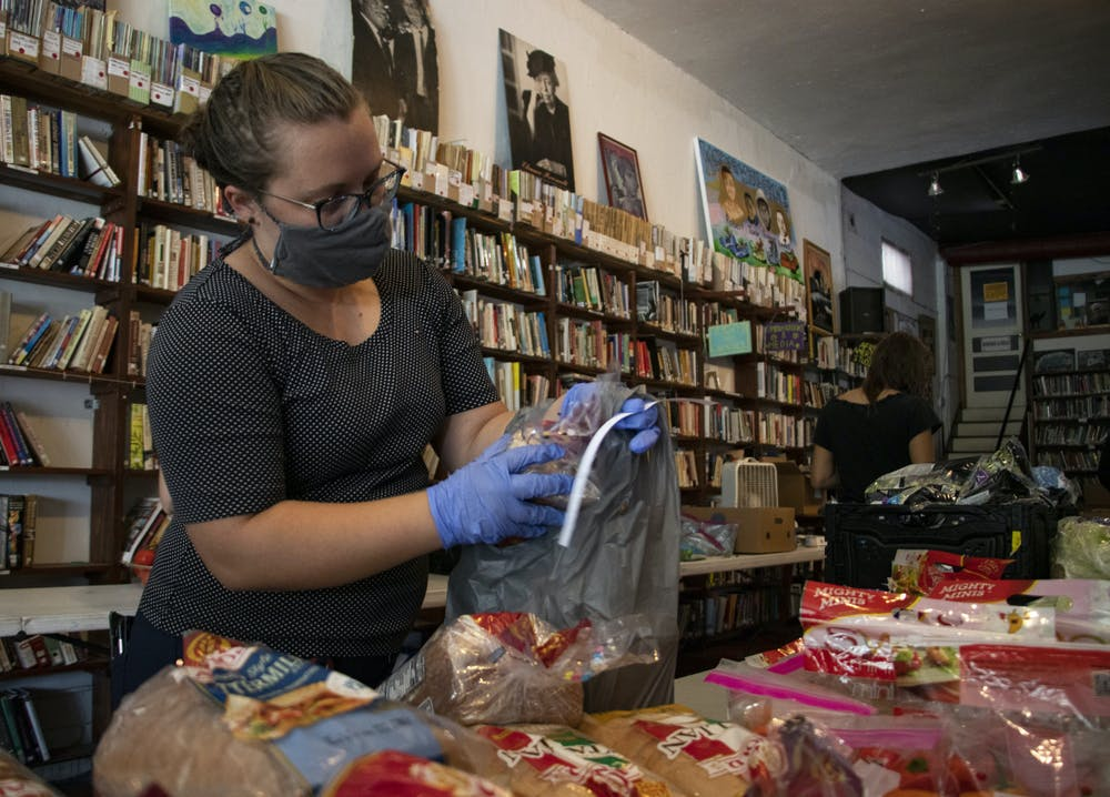 """Miranda Carver Martin packs a bag with groceries for the Free Grocery Store at the Civic Media Center on Friday, Aug. 27, 2021. """"I want to live in a world where people take care of each other,"""" Martin said."""