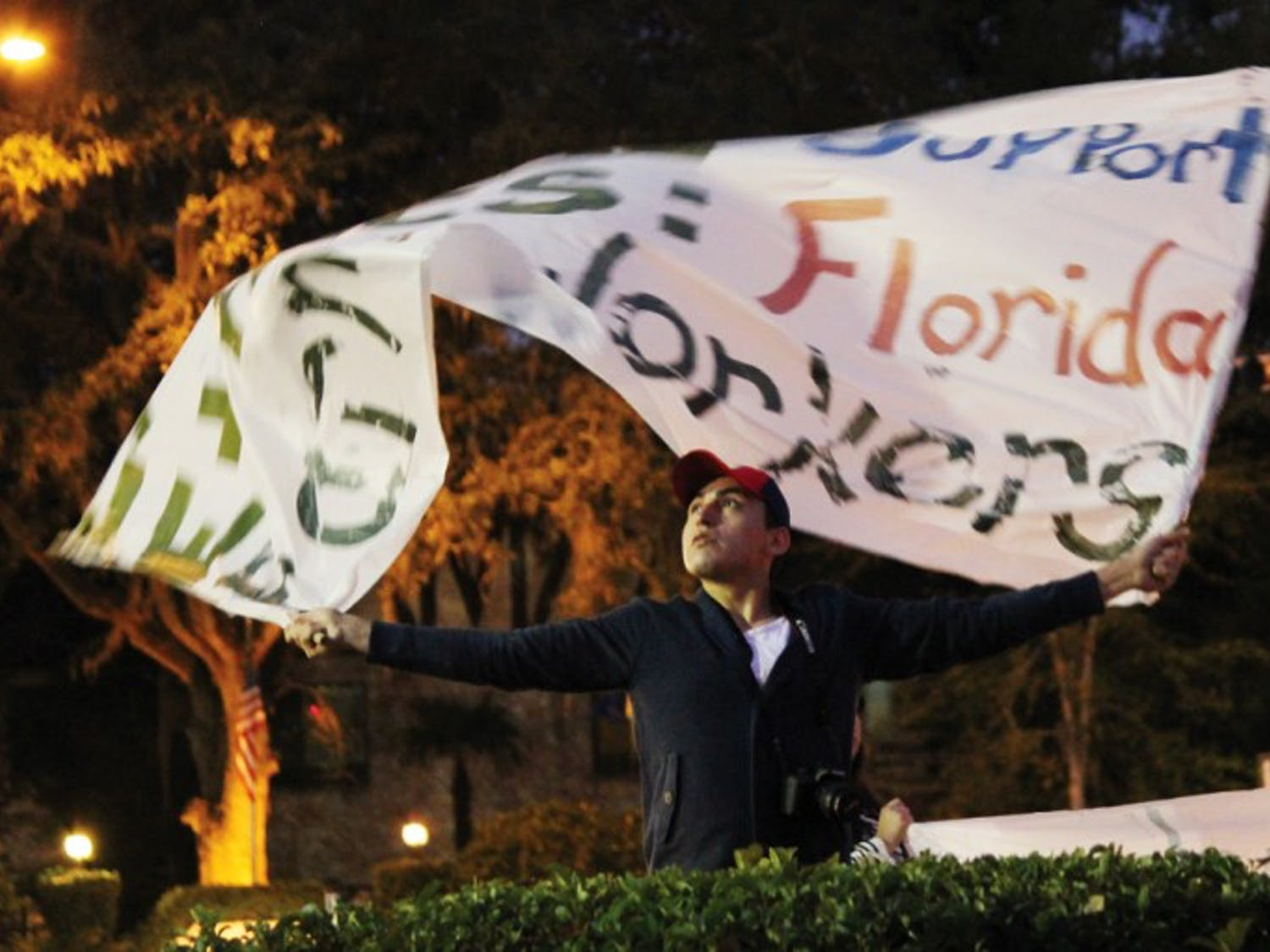"""Julio Mora, a 22-year-old architecture junior, hoists a banner that reads, """"Expand Support Ethics: Florida Farm Workers,"""" at a protest by the Interfaith Alliance for Immigrant Justice group at the Publix on 34th Street and University Avenue Monday night."""