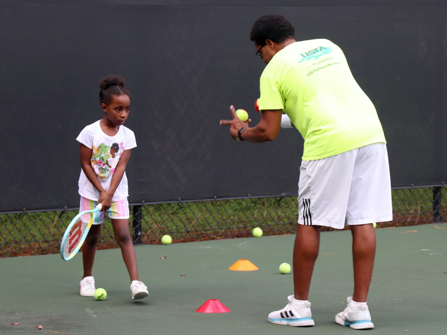 Lainey Norton (left), 6, attends a tennis lesson led by Christopher Scott Champion (right), 35, during the program at T.B. McPherson Park on Thursday, Sept. 23, 2021. The pilot program offers discounted lessons for East Gainesville residents.