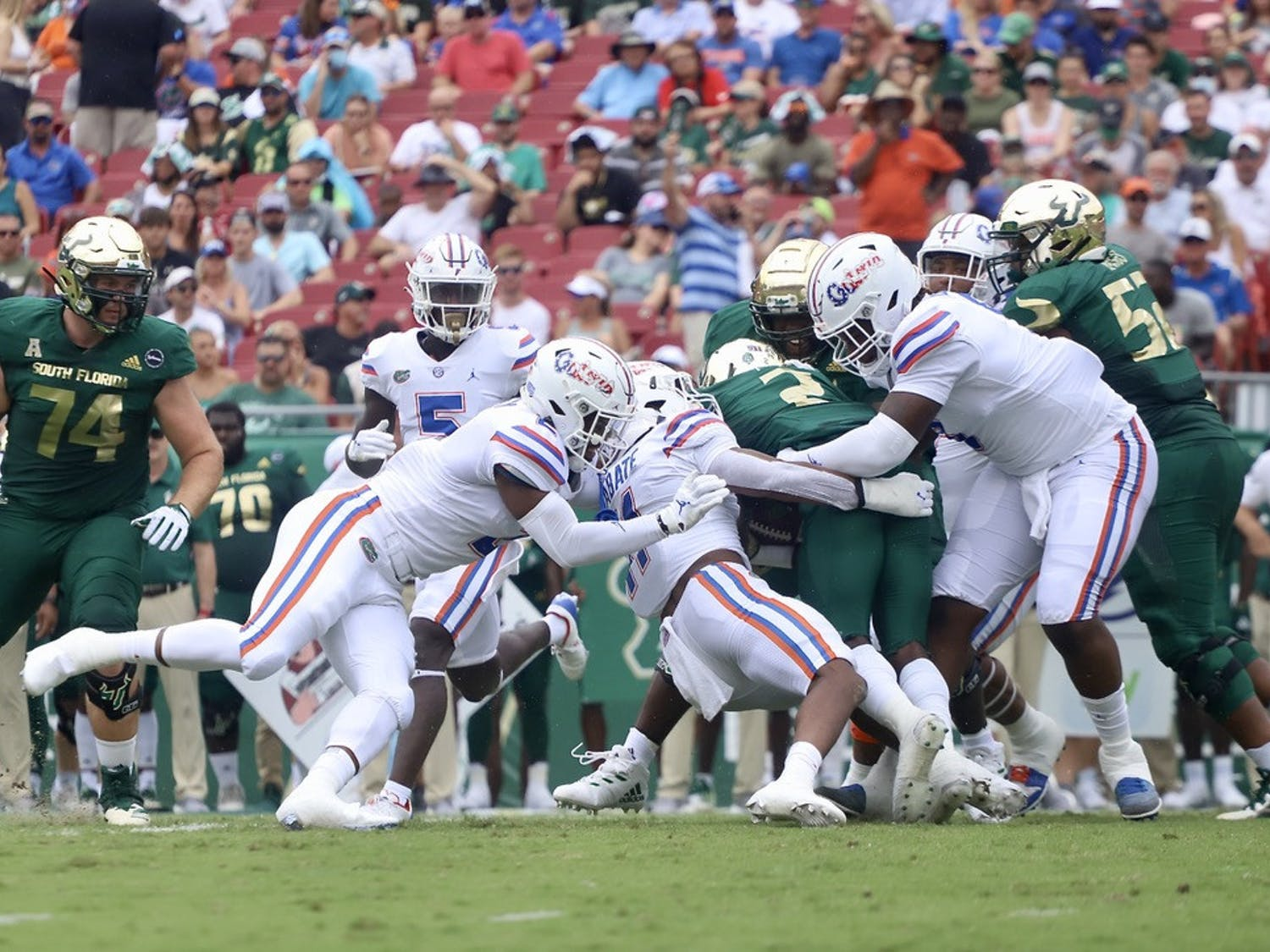 Florida's Mohamoud Diabate (11) and two other Gators tackle USF running back Darrian Felix during their 42-20 victory on Sept. 11.