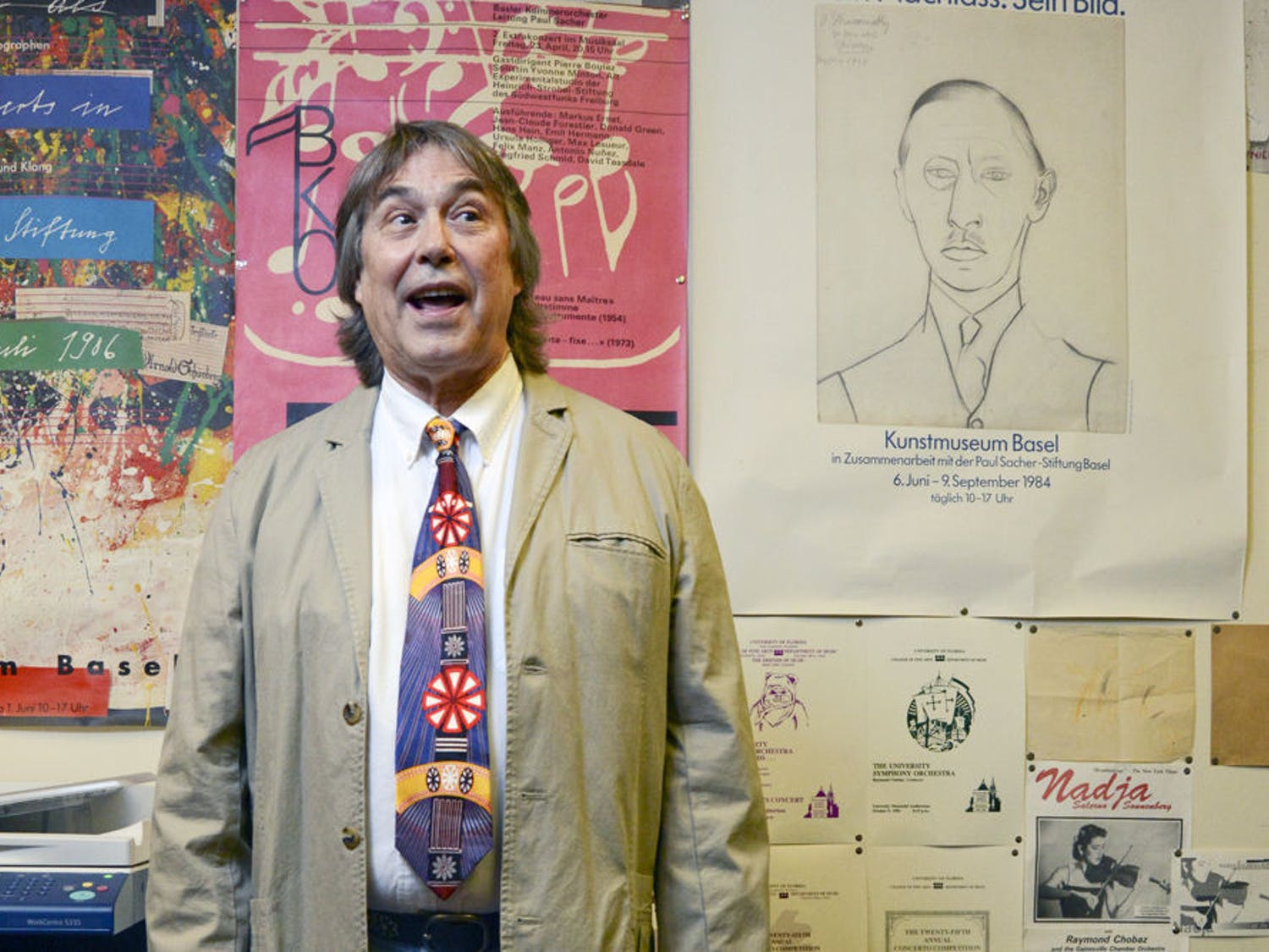 Amid posters of concerts, composers and teachers, Raymond Chobaz poses for a photo in his office in the Music Building. A native of Switzerland, Chobaz left his country at the age of 24 to pursue music education in the U.S.