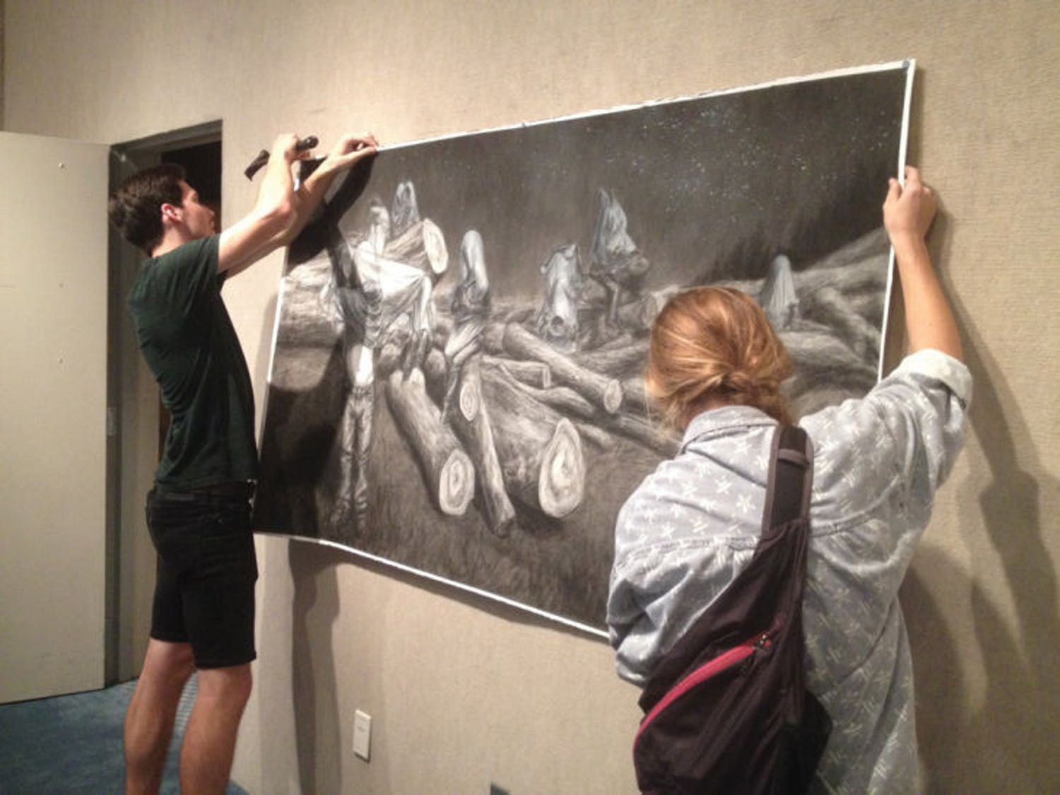 """Zac Thompson and Hannah Dwyer hang a drawing for the """"Quarantined"""" exhibition inside the Gallery at the Reitz Union. The opening reception is from 7 to 9 p.m., and their work will be on display through Dec. 5."""