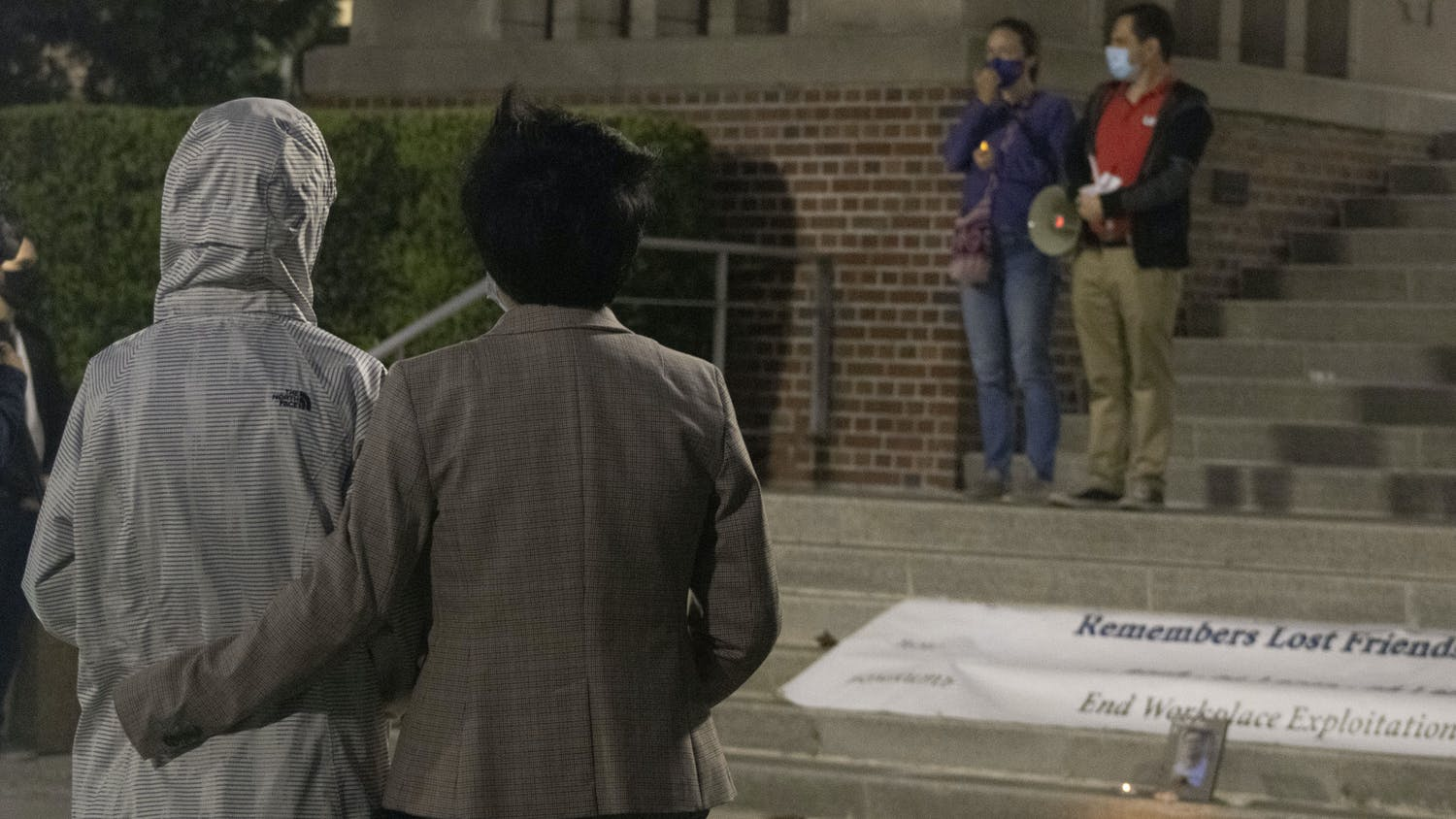 Two attendees stand in front of Tigert Hall at UF during a vigil on Thursday, April 1 honoring the life of international graduate student Huixiang Chen, who died by suicide in 2019. UF's Graduate Assistants United organized the event to express frustrations over abusive graduate student-mentor relationships.