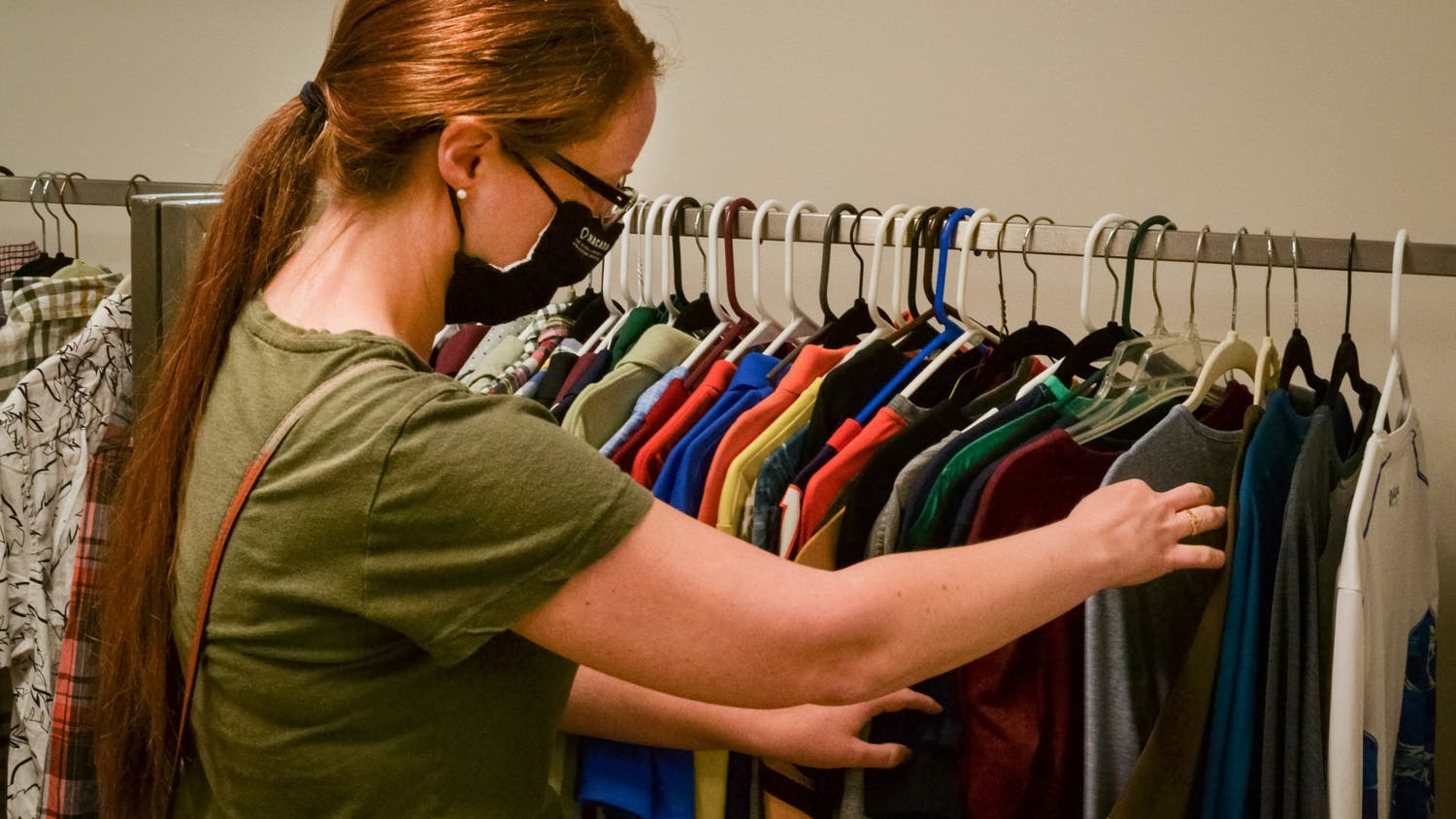 UF-lecturer Kelly Medley, 35, sifts through racks of used clothes at the Humane Society's new boutique thrift store, located at 5403 Southwest Archer Road on Sunday, June 6, 2021. The boutique store receives some of the local Humane Society's higher-end items, such as designer handbags and vintage musical instruments.
