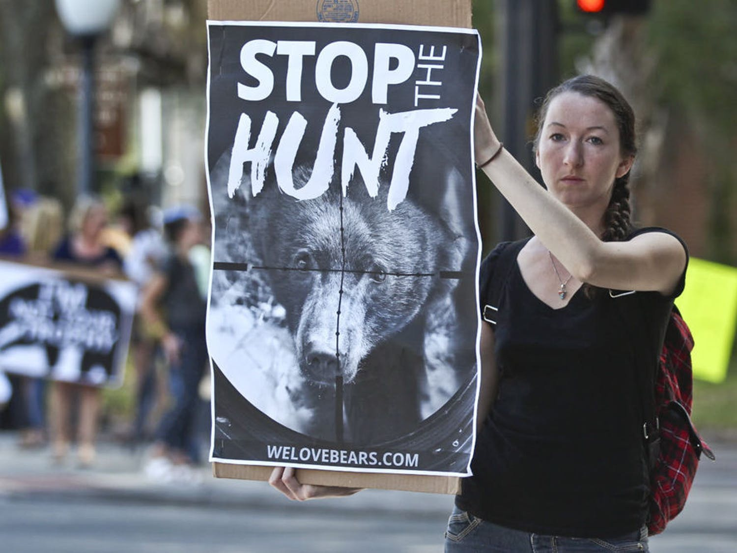 """Karrie Ford, 27, protests against the Florida bear hunt at the Stop the Bear Hunt Rally at the intersection of Main Street and University Avenue on Oct. 23, 2015. """"The number of bears in Florida versus the number of hunting permits sold just doesn't make sense,"""" she said."""