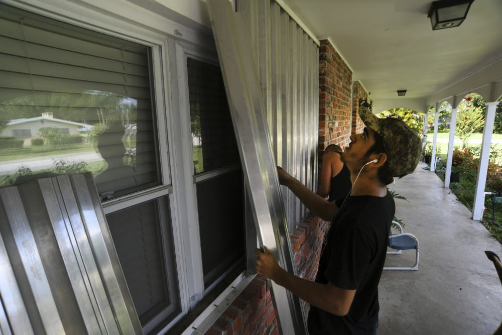 <p>Richard Henson (foreground) and his uncle, Peter Henson, prepare their grandmother's house Thursday, Aug. 29, 2019, where she lives on Greenwood Drive in Fort Pierce, Fla., for the arrival of Hurricane Dorian. (Eric Hasert/TCPalm.com via AP)</p>