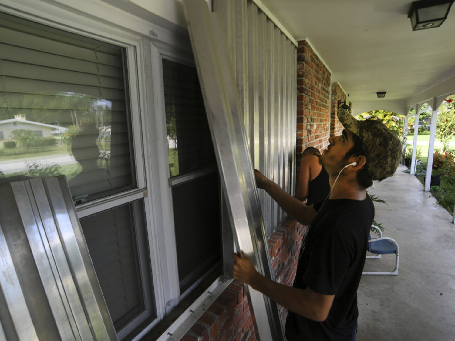 Richard Henson (foreground) and his uncle, Peter Henson, prepare their grandmother's house Thursday, Aug. 29, 2019, where she lives on Greenwood Drive in Fort Pierce, Fla., for the arrival of Hurricane Dorian. (Eric Hasert/TCPalm.com via AP)