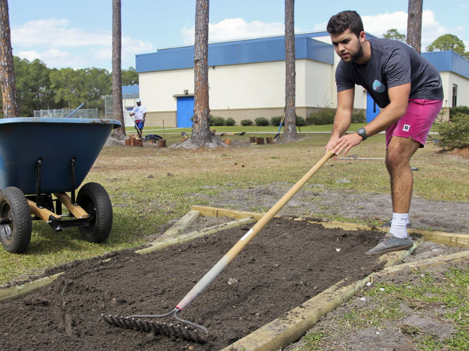 Jack Cheney, a UF marketing freshman, levels out dirt by the playground at Marjorie Kinnan Rawlings Elementary School on Sunday. The 18-year-old volunteered as part of a landscaping team during Project Makeover.