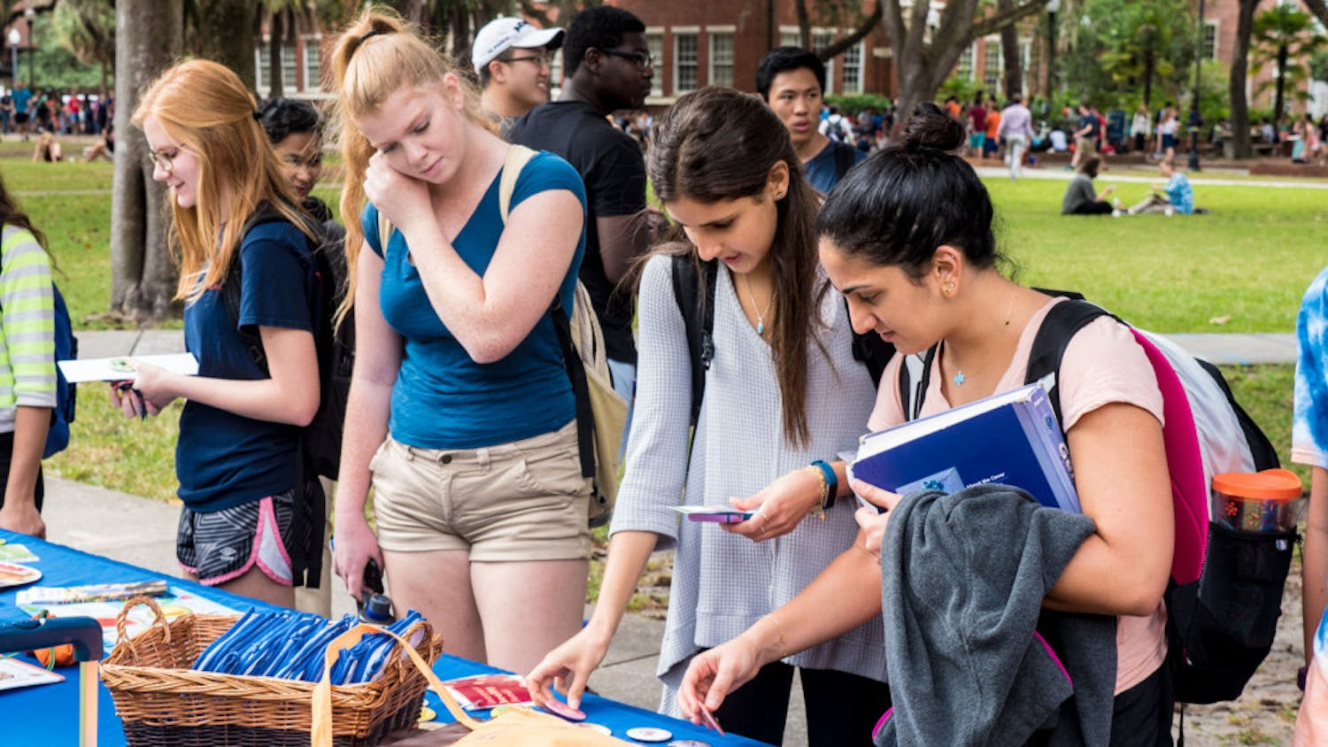 UF health education senior Tala Rizkallah, 21, and UF communication sciences and disorders senior Michelle Saade, 21, check out health-oriented pins at the GatorWell table at the Freshman 15 Wellness Fair on the Plaza of the Americas on Wednesday afternoon.