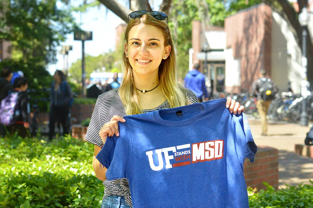 "<p>Julia Tiplea, a 19-year-old marine science sophomore, hands out ""UF stands with MSD"" T-shirts to fundraise for her group's trip to Washington for the national ""March for Our Lives"" event Saturday.</p>"