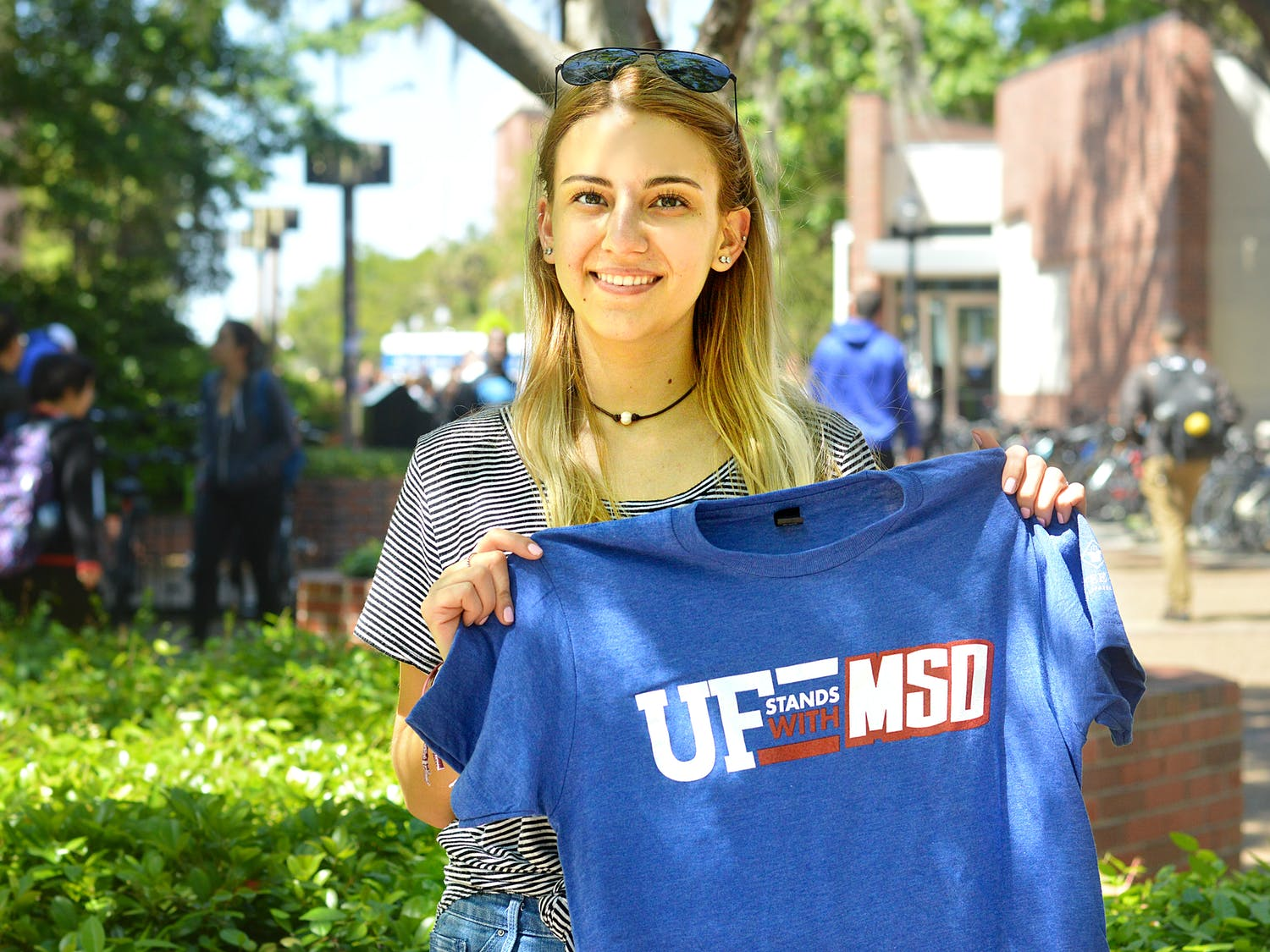 """Julia Tiplea, a 19-year-old marine science sophomore, hands out """"UF stands with MSD"""" T-shirts to fundraise for her group's trip to Washington for the national """"March for Our Lives"""" event Saturday."""