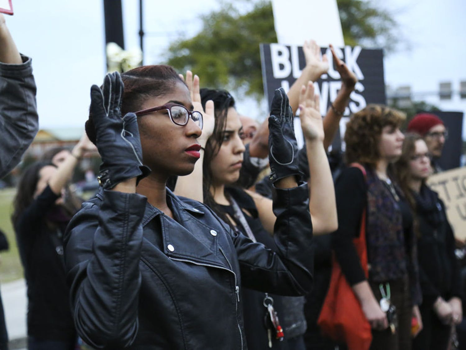 Ashley Dunbar, a 24-year-old UF law graduate student, raises her hands during the #BLACKSLIVESMATTER march at the intersection of 13th Street and University Avenue Monday afternoon.