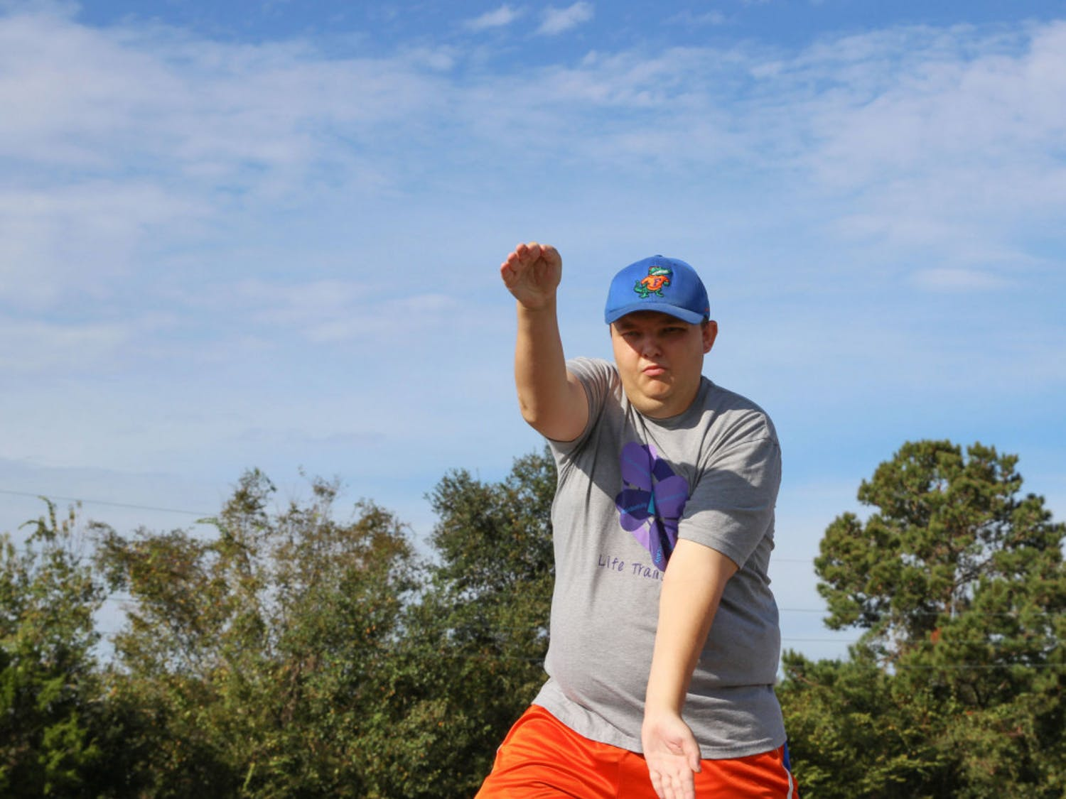 """24-year-old Billy Moody gives a big Gator chomp during his walk at theFourth Annual """"Run With The Cops"""" walk locatedat the Santa Fe track. This was Moody's second time attending the walk, and he wasaccompaniedby fellow members of the """"Life Transition Skills""""organization."""