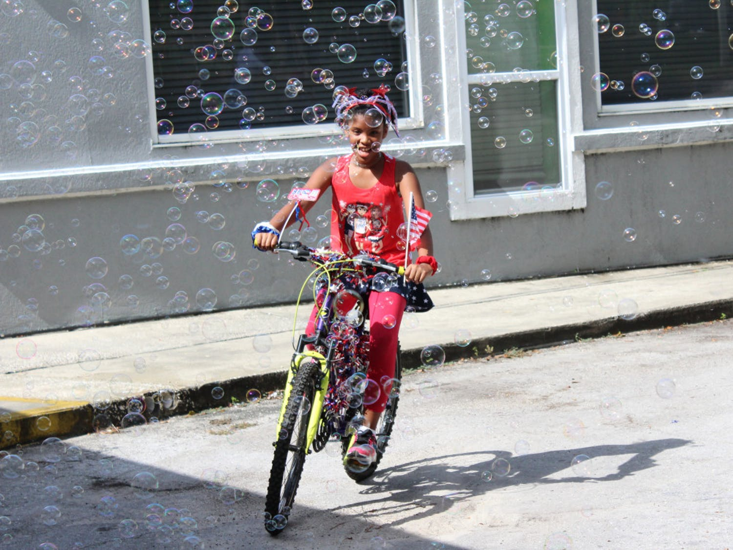 """Bouncers held its second annual Fourth of July Bicycle Parade with a turnout of less than a tenth of what it was in 2019. A year prior, 100 kids attended. This year, only eight came to ride their bicycles, tricycles, and scooters around the parking lot. Angie Adams, manager of Bouncers Indoor Playground, attributed the reduced turnout to the pandemic but proceeded with the event because she says """"It's still important to celebrate the Fourth of July."""""""
