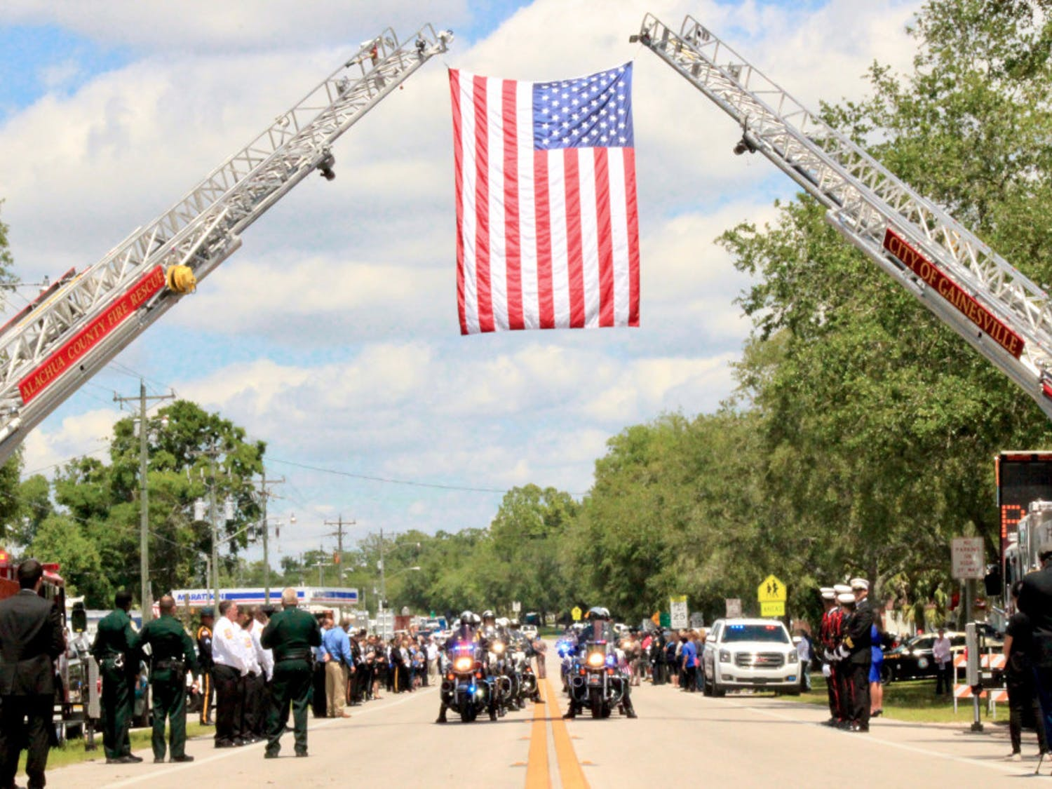 A group of law enforcement officers drive under the U.S. flag hoisted by Alachua County Fire Rescue and Gainesville Fire Rescue fire engine ladders as part of the funeral procession on South Main Street in Bell, Florida for the two deputies who were shot in Trenton.