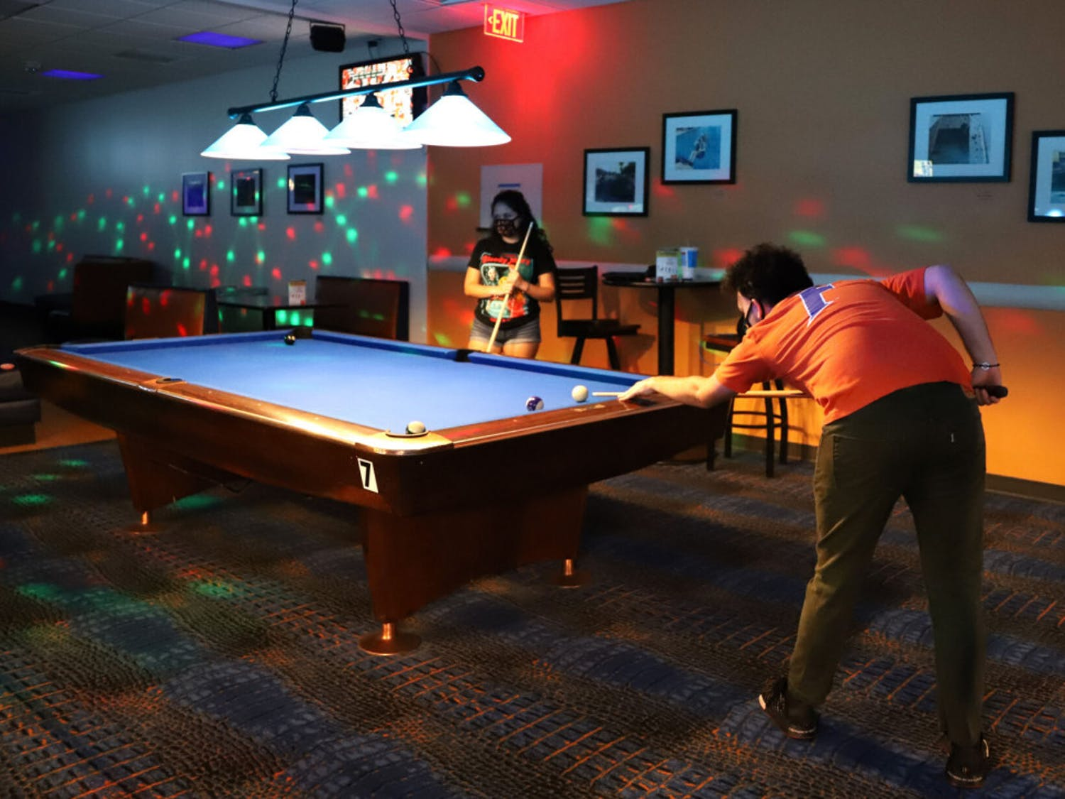 Max Slabbinck (right), 22, a senior media and society student, and Averi Hemingway, 21, a recent telecommunication graduate, shoot pool at the Reitz Union Game Room on Oct. 10, 2020. To ensure social distancing, the two pool tables nearest to Slabbinck and Hemingway are covered and face masks are required at all times.