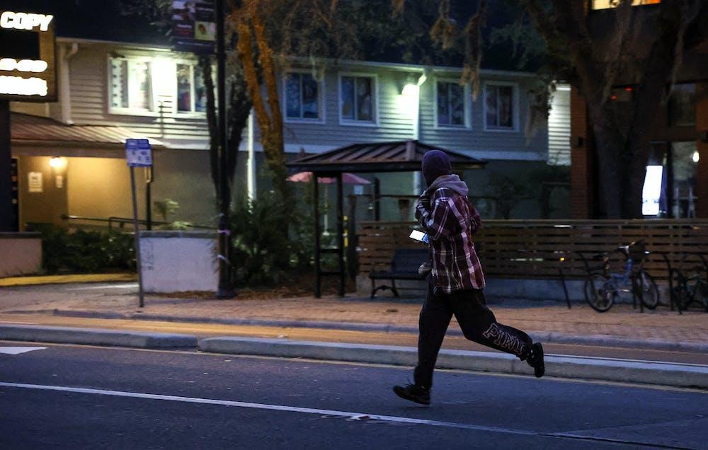 <p>A pedestrian jaywalks across West University Avenue on Wednesday, Feb. 17, 2021.</p>