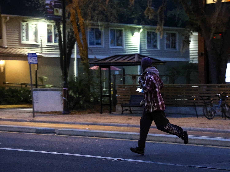 A pedestrian jaywalks across West University Avenue on Wednesday, Feb. 17, 2021.