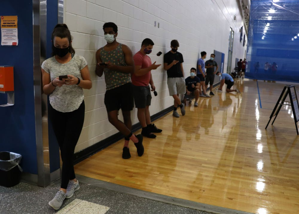 <p>People stand in line to enter the weight room at the Southwest Recreation Center in Gainesville on Monday night, Sept. 21, 2020. According to recsports.ufl.edu, the weight room is open at limited capacity, however the website does not state how many people are allowed at one time.</p>