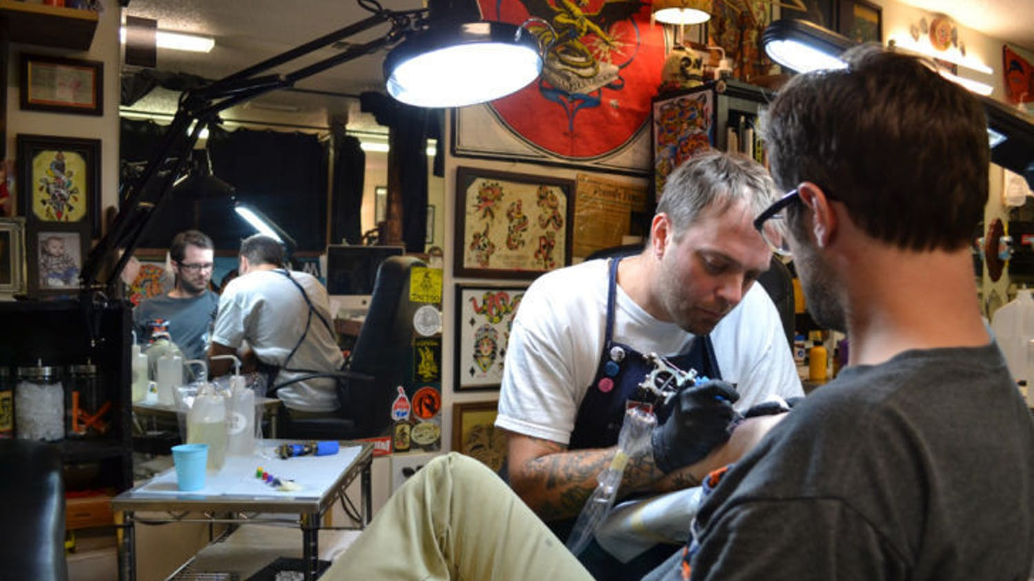 Mike Salay, 39, owner of Anthem Tattoo Parlor, tattoos Rich Mal, 29, the shop's tattoo apprentice. The parlor is relocating April 15 to 230 NW Second Ave.