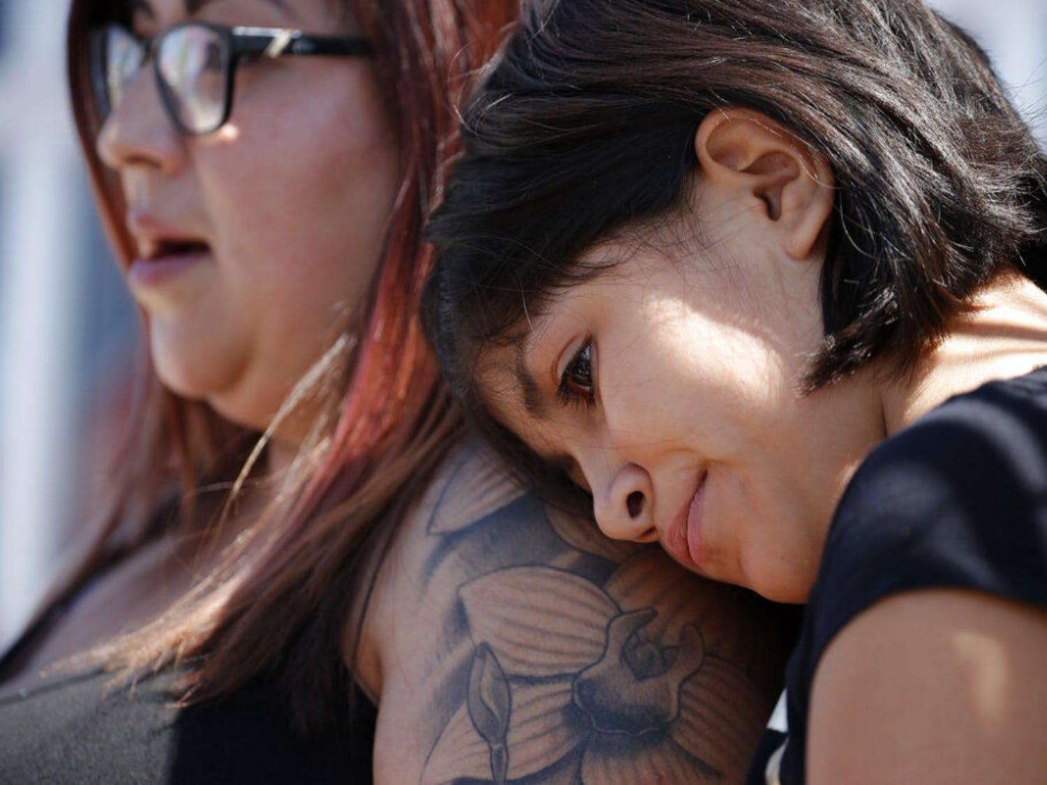 Eleven-year-old Leilani Hebben puts her head on her mother Anabel Hebben's shoulder as they visit the scene of a mass shooting at a shopping complex Sunday, Aug. 4, 2019, in El Paso, Texas.
