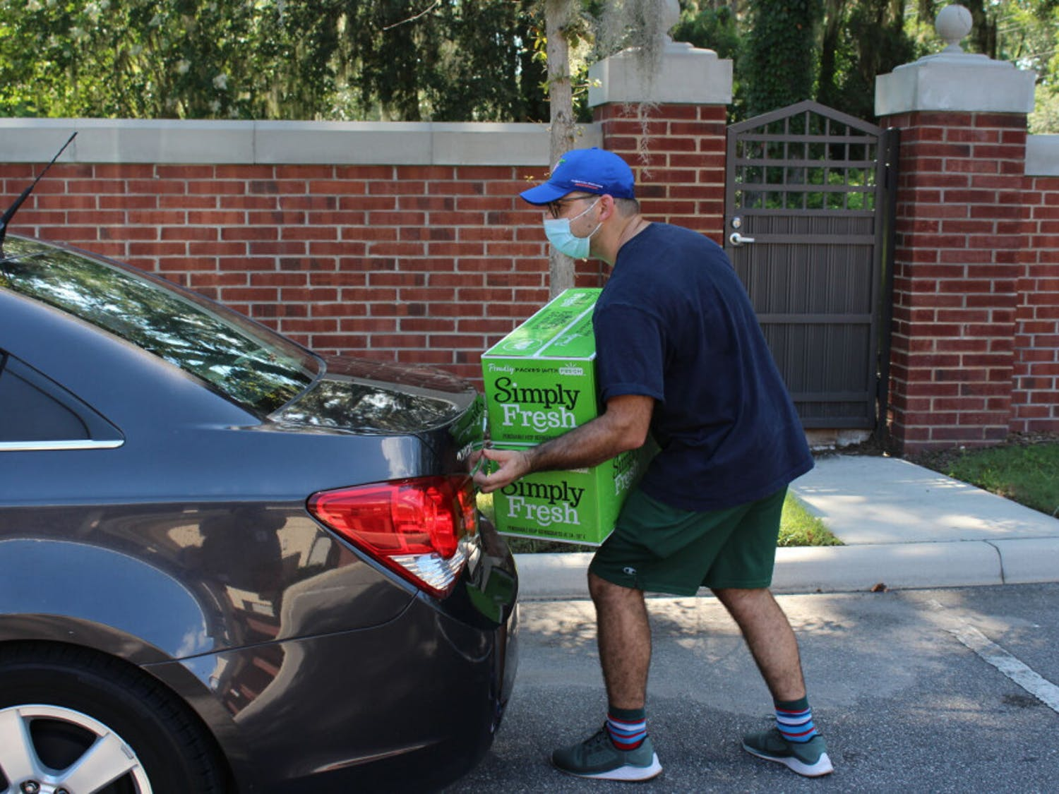 Hanan Walters, a recent University of Florida graduate with a degree in economics, loads boxes into the trunk of a car. Walters is an active member of the Lubavitch Chabad Jewish Center of Gainesville and frequented the weekly Friday dinners, and spent the afternoon of July 16 volunteering to haul boxes and direct traffic at the drive-through food drive.