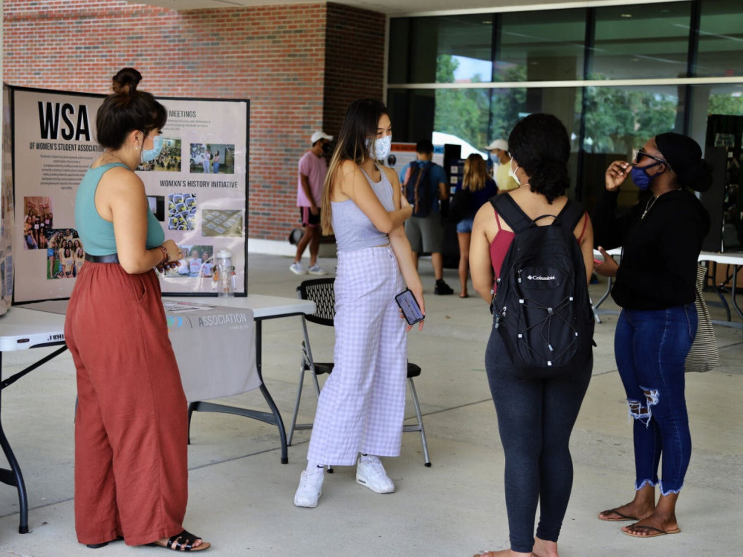 """Lynne Imamura (left), 21, a fourth-year political science student and Mary Nguyen (right), 21, a fourth-year nutritional science student speak about the UF Women's Student Association at a tabling event held at the Reitz Union on September 4, 2020. """"We invite women and others who are cis-gender and we provide a safe space for them to talk about women's issues,"""" Nguyen said."""
