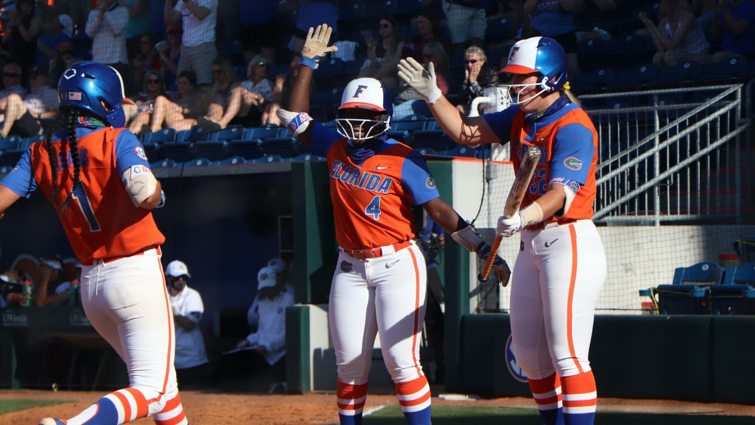 Charla Echols, Hannah Adams and Kendyl Lindaman celebrate at home plate. The Gators handled the Aggies 4-0 Saturday.