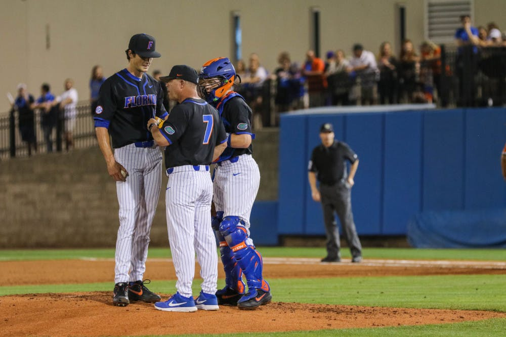 <p>UF pitcher Tommy Mace (left) speaking with coach Kevin O'Sullivan (middle) and catcher Brady Smith (right) during the UM series last year.</p>
