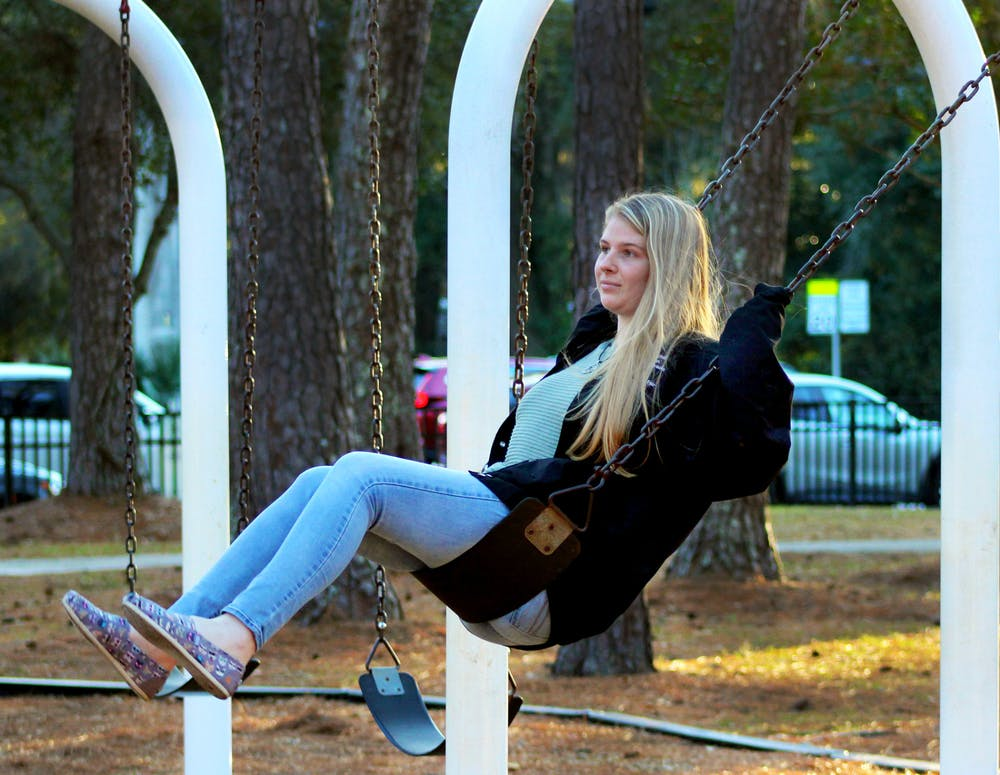 "Ashley Sturgill, 19, Santa Fe biology sophomore, swings on the Albert ""Ray"" Massey Park swing-set in Gainesville on Thursday, Jan. 14, 2021."