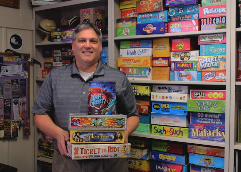 Jeromy Koffler stands in front of his collection of board games in his office at UP. He owns 405 board games.