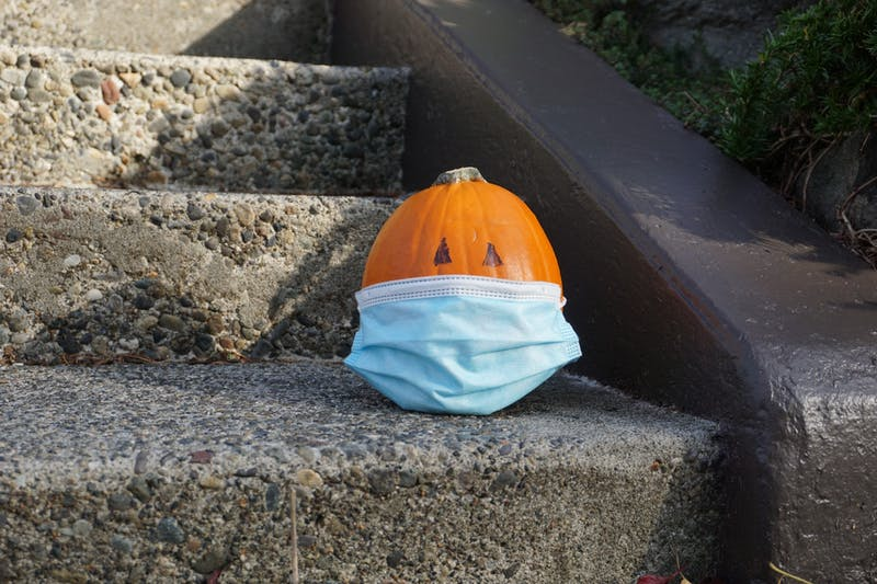 A pumpkin sits alone wearing a mask. Halloween this year will require masks and distance.Photo Illustration by Marek Corsello